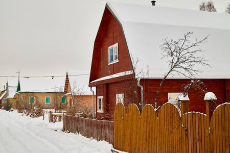 Village in a winter day in snow. Rural and rustic landscape in a cold day in Russia