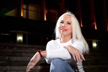 Ugly woman with white blonde hair on the steps of stair in the city at night with lighting flashes in the black background
