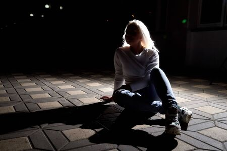 Ugly woman with white blonde hair in the city at night with lighting flashes in the black background