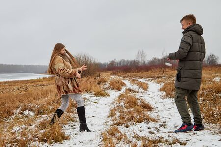 Romantic couple in love on autumn or winter walk outdoors. Natural scenery. Field with yellow grass and path covered with snow