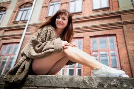 Brunette girl near near the facade of a large red brick building with windows in the Central part of the ancient city. Walk in downtown. Portrait of a funny pretty girl on the street of the town 版權商用圖片 - 133772966
