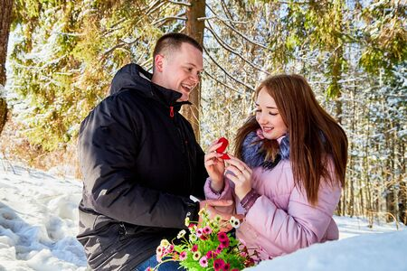 Marriage proposal. Guy gives engagement ring at red box to his girl in a winter forest full of snow 版權商用圖片