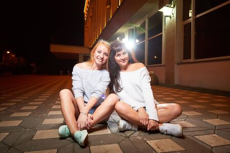 Two female friends on a city street at night. Girls and black background with light outdoors in evening time 版權商用圖片