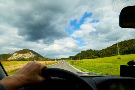 View of the road with a beautiful mountain landscape from the car window in a nice summer or autumn day. Woman's hand on the steering wheel. Female driver seeing beautiful landscape during travel 版權商用圖片 - 133773047