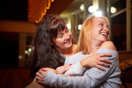 Two female friends having fun on a city street at night. Girls near illuminated building and black background with light outdoors in evening time