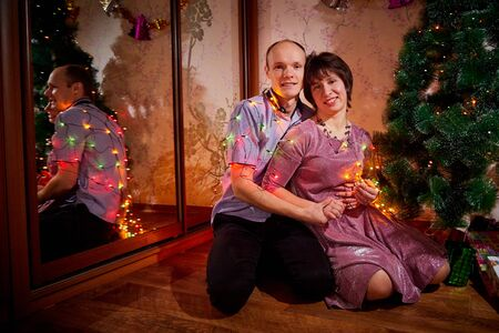 Adult couple staying at home together on holiday evening and sitting on floor in front of christmas tree and hugging. Cute romantic lovers in New Year in the room