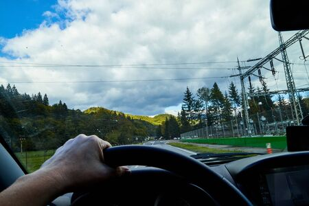 View of the road with a beautiful mountain landscape from the car window in a nice summer or autumn day. Womans hand on the steering wheel. Female driver seeing beautiful landscape during travel