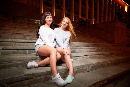 Two female friends on the stairs near the illuminated building in a city street at night. Girls and black background with light outdoors in evening time 版權商用圖片