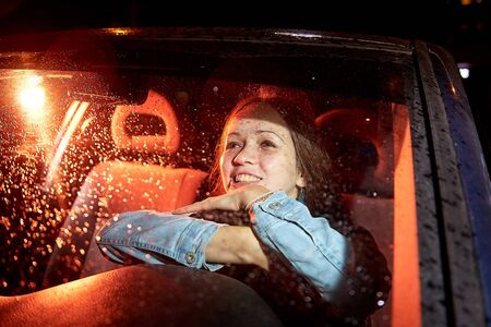 Beautiful young woman in the car at night with light background 版權商用圖片