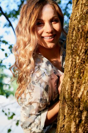 Beautirul girl with curly blonde hair near a tree in the park with sunny weather in a summer, spring or autumn day