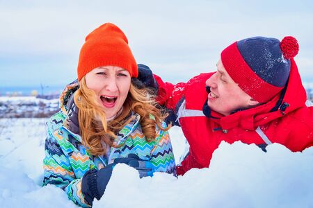 Happy pair of male and female in warm clothes together outside in field in a winter day 版權商用圖片