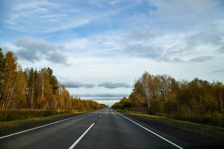 Track from the car window and white clouds on blue sky. Driver seeing beautiful autumn landscape during travel in auto