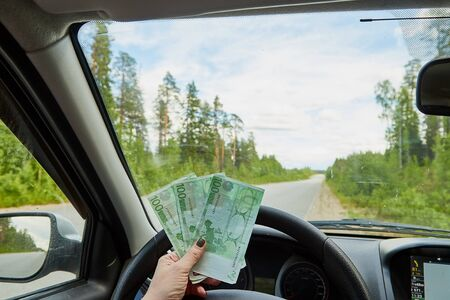 Euro banknotes in a woman hand inside of a car and road with nature outside Stockfoto