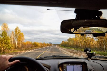 Kirov, Russia - October 03, 2018: Track from the car window and white clouds on blue sky. Womans hand on the steering wheel. Female driver seeing beautiful autumn landscape during travel in auto Stockfoto