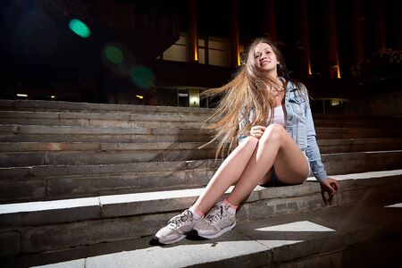 Young beautiful brunette woman with long hair on the steps of stairs on a city street at night and colored lights of flash near her