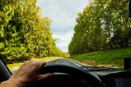 Track from the car window and white clouds on blue sky. Womans hand on the steering wheel. Female driver seeing beautiful autumn landscape during travel in auto