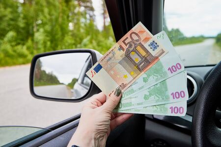 Euro banknotes of various denominations in a woman hand inside of a car and road with nature outside
