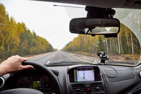 Kirov, Russia - October 03, 2018: Track from the car window. Womans hand on the steering wheel. Female driver seeing autumn landscape during travel in auto