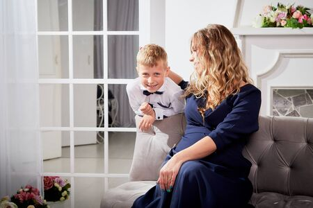 Beautiful elegant pregnant woman with blonde curly hair with small boy in the room. Mother having fun with young son in living room. Maternity concept