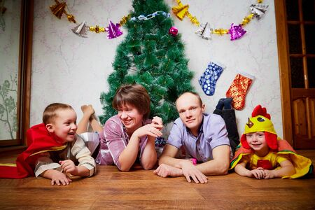 Family consisgitng mother, father and two brothers in carnival costumes at Christmas or new year near the Christmas tree in the room. Mom, dad and boys indoor posing together Stockfoto