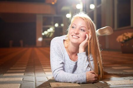 Blonde girl near glowing building on the street of night city and black background with light. Walk and photoshoot outdoors in the evening Stockfoto