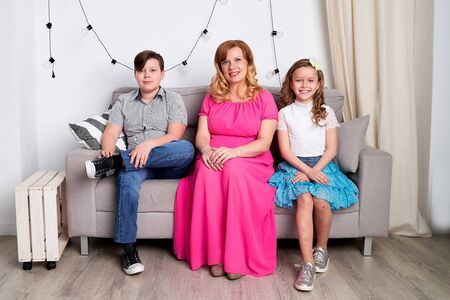 Pregnant mother with her two children at home during photoshoot. Mothers Day in living room with mom, son and daughter