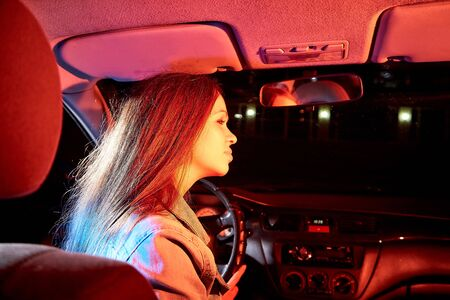 Beautiful young woman in the car at night with light background Stockfoto