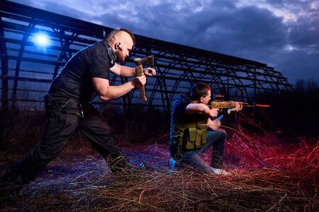 Soldier and instructor at night outdoors. A short man paratrooper and a large brutal male instructor during a military exercise dark night at the military training ground Imagens