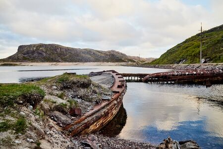 Graveyard of old ships in Teriberka in Russia. Destroyed ships in the water in a summer, spring or autumn day or morning