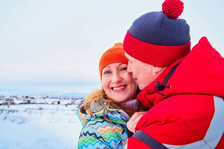Happy pair of male and female in warm clothes together outside in field in a winter day Stockfoto
