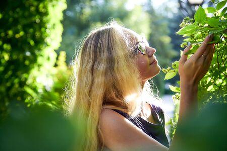 Hübsches Teenager-Mädchen 14-16 Jahre alt mit lockigen langen blonden Haaren im schönen Erwachsenenkleid im grünen Park an einem Sommertag im Freien. Schönes Outdoor-Porträt