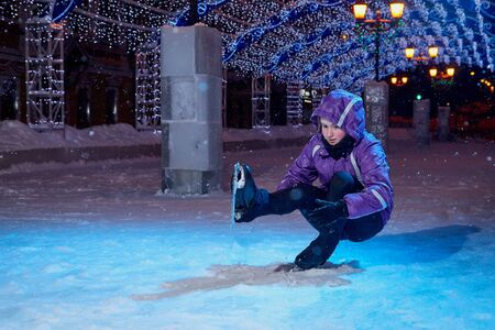 Girl skating on the ice arena full of light on the city square in winter evening. Photo shoot with a teenager female athlete with blue lights on a snowy winter night
