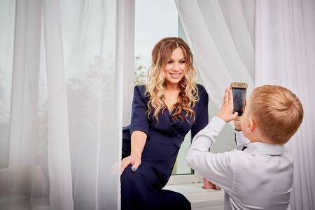 Beautiful elegant pregnant woman with blonde curly hair with small boy in the room. Future mother having fun with young son in nice dress at home in living room. Maternity concept