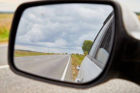 Die Reflexion der Straße im Seitenspiegel am Herbsttag. Reisekonzept mit Feld