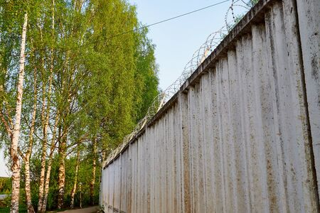High concrete fence with barbed wire on summer day Banque d'images