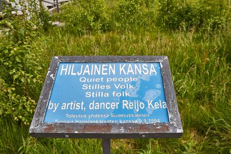 SUOMUSSALMI, FINLAND - JULY 24, 2019: A sign near the field with the group of objects in people clothes which looks like crowd in the field in a summer of autumn. Installation Reijo Kela Silent People