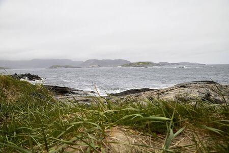 Norwegen-Landschaft mit felsigem Ufer des Nordmeeres bei bewölktem Wetter an einem Sommer-, Frühlings- oder Herbsttag