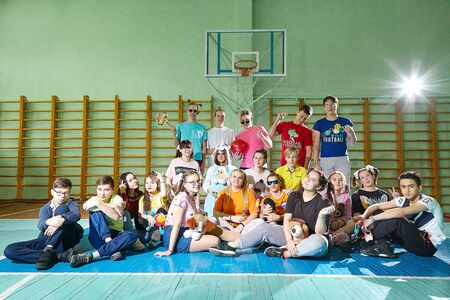 Kirov, Russia - September 28, 2019: Big group of student or schoolchildren in funny dress in gym. Teenagers posing together in sport place