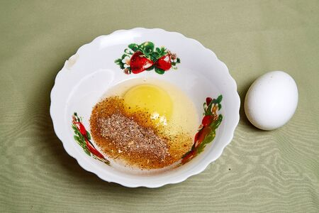 Raw egg on a white plate on the table. Preparing eggs for cooking Archivio Fotografico - 137052770