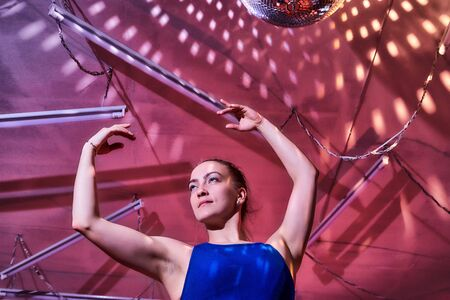 Flexible gymnast girl standing in hall or on stage with interesting light. Portrait of young woman in sport dress. Performance and posing dancing model. Sport, training, active lifestyle concep Archivio Fotografico - 137225468
