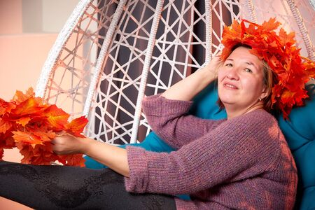 Ugly aged woman in a sweater with a wreath of yellow autumn maple leaves in a white wicker hanging chair in the room with curtains. Old model during photoshoot in studio Archivio Fotografico - 137225475