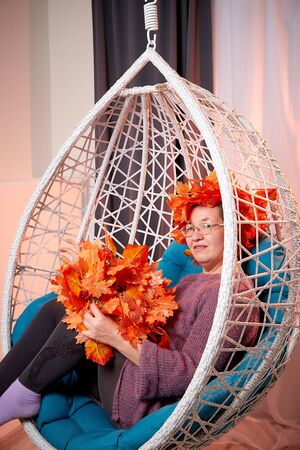 Ugly aged woman in a sweater with a wreath of yellow autumn maple leaves in a white wicker hanging chair in the room with curtains. Old model during photoshoot in studio Archivio Fotografico - 137225481