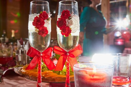 Two glasses decorated with red flowers and bows on the Banquet table and nice light behind Archivio Fotografico - 137329587