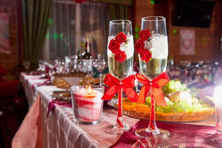 Two glasses decorated with red flowers and bows on the Banquet table and nice light behind Archivio Fotografico - 137329606