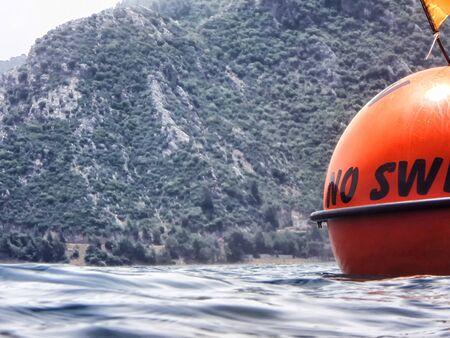 Zeeoppervlak met boeien met woorden Geen zwemmen en bergen in de verte. Bekijken en fotograferen vanaf het water op een zomerse dag Stockfoto