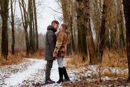 Romantic couple in love on autumn or winter walk outdoors