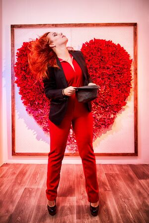 Beautiful young woman with redhair and black hat being near white wall with red heart indoors 版權商用圖片