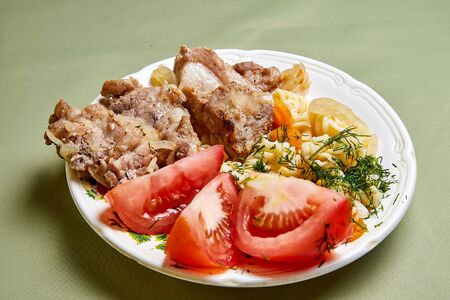 Cooking. Grilled meat on a plate with garnish and tomatoes indoors