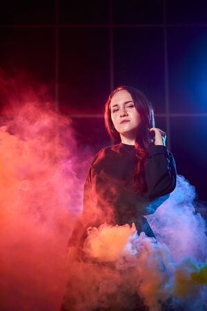 Portrait of chubby teen girl during photoshoot with colored smoke at night and black background. Model in a photo shoot with colored light