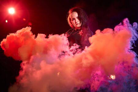 Portret van mollig tienermeisje tijdens fotoshoot met gekleurde rook 's nachts en zwarte achtergrond. Model in een fotoshoot met gekleurd licht
